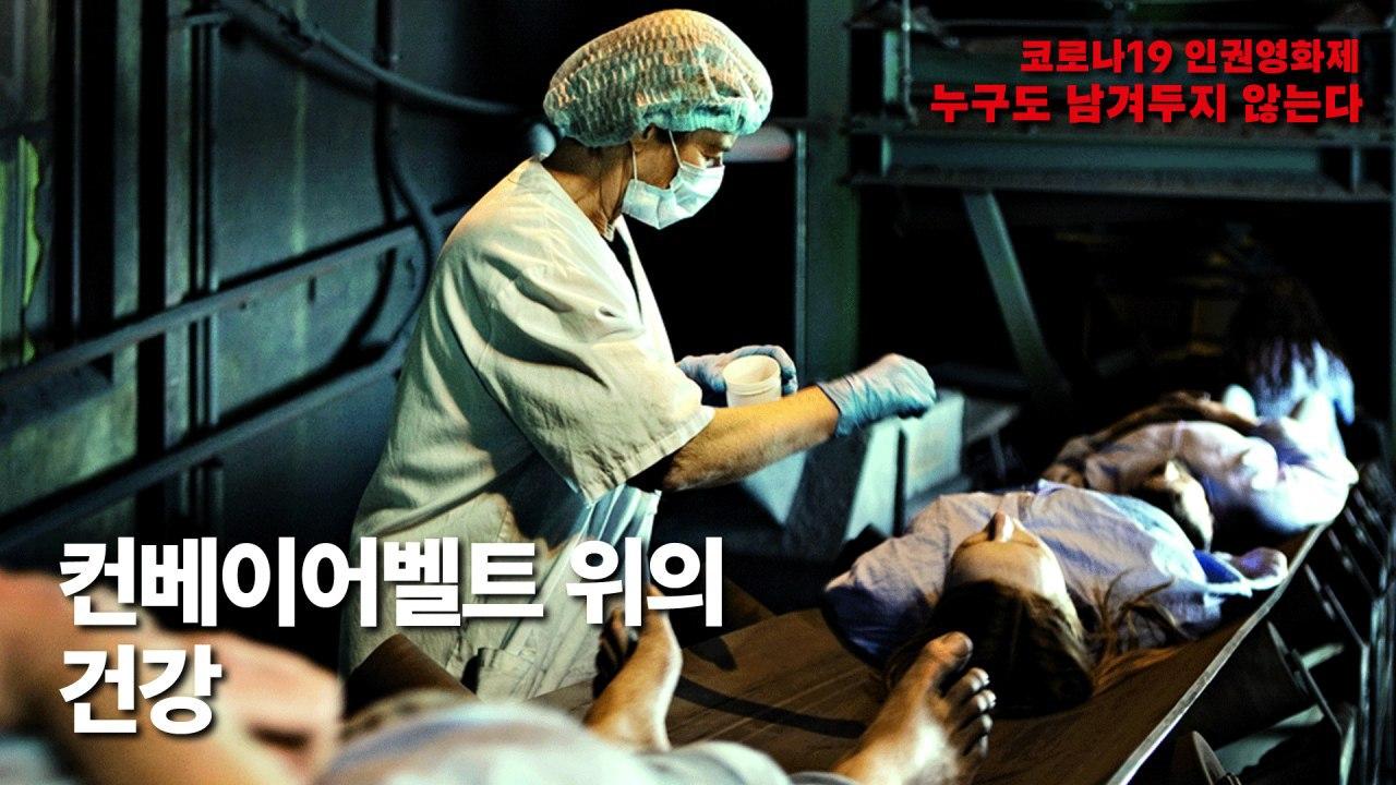 그림1. <컨베이어벨트 위의 건강>의 스틸컷. 컨베이어 벨트 위에 환자복을 입은 사람들이 누워 있다. 한 의료인이 약을 들고 있다.