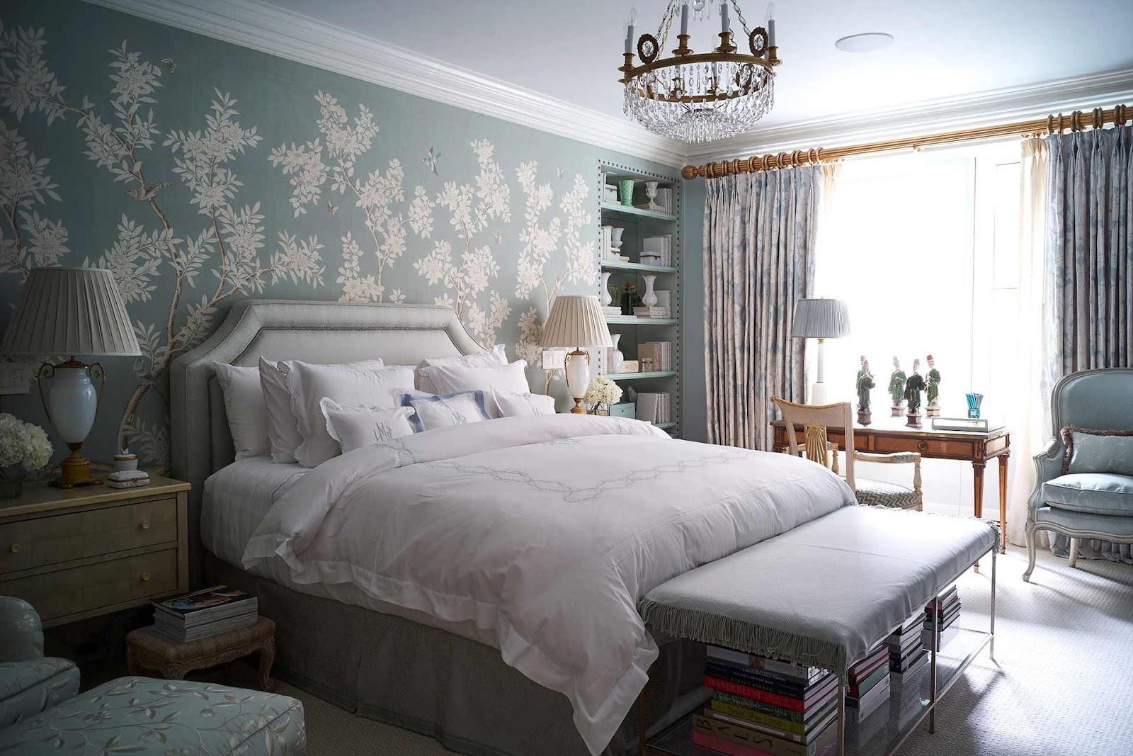 Quarto com cama de casal, papel de parede, abajur e poltronas.
