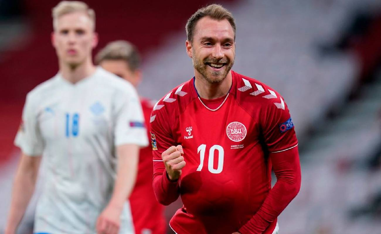 Alt: Denmark's Christian Erikson celebrates with the ball in his shirt - Photo by LISELOTTE SABROE/Ritzau Scanpix/AFP via Getty Images