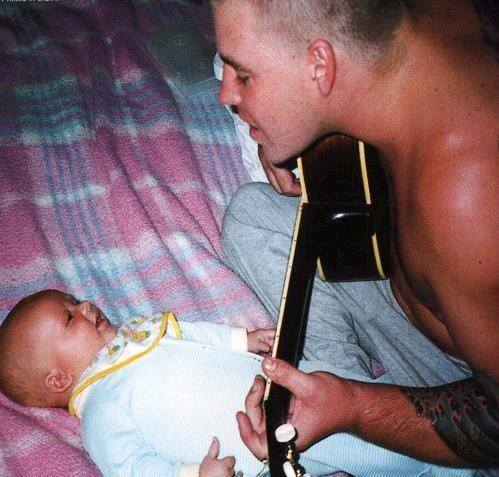 Bradley Nowell playing the guitar to his 11 month old child