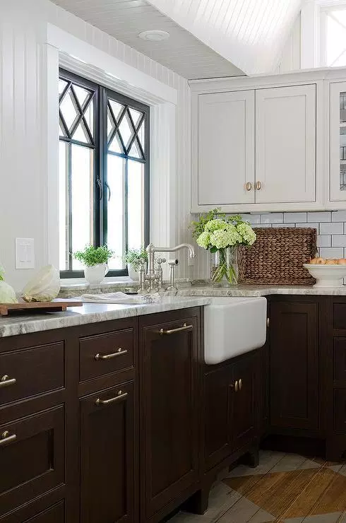 farmhouse kitchen with two toned cabinets in dark brown and white. the cabinets are shaker style with simple silver hardware. a farmhouse sink overlooks the window, giving it a country rustic feel