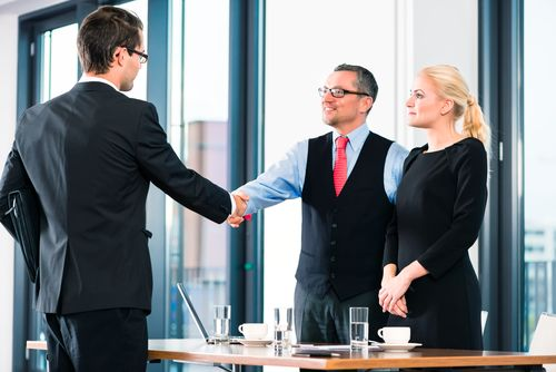 a male interviewer shaking the hands of a candidate while the female interviewer watches. They are all standing.