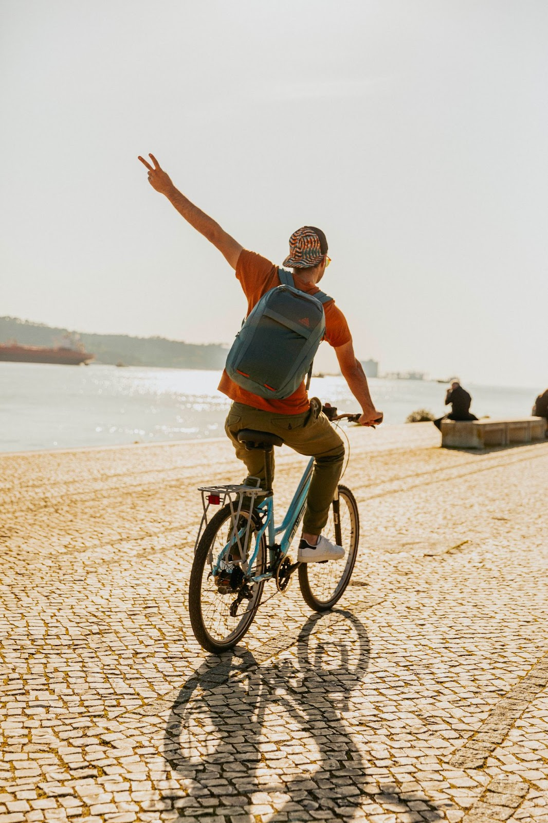 A man on a bicycle throws a peace sign.