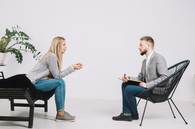 Male psychologist sitting in front of female patient listening to her problem Free Photo