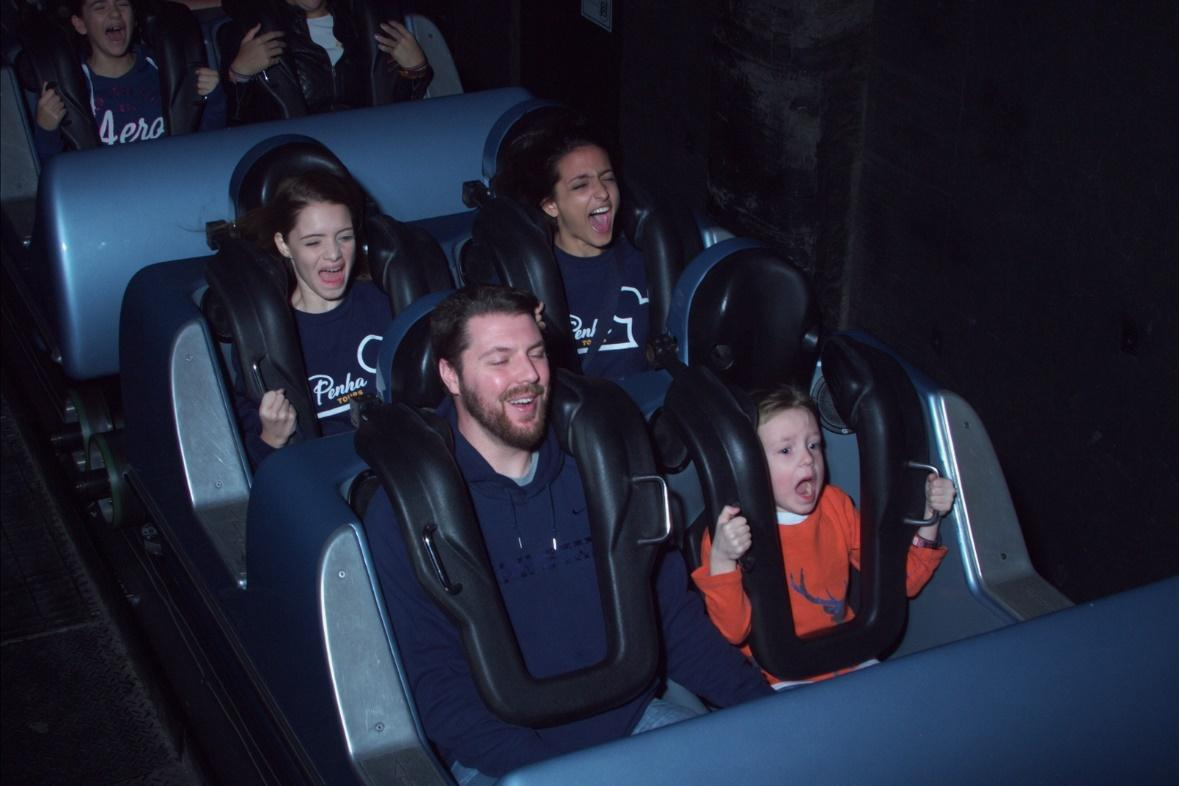 Disney's Memory Maker photo captures a smiling dad and his terrified (but in a happy way) boy on a roller coaster ride, two girls also scream behind the males.