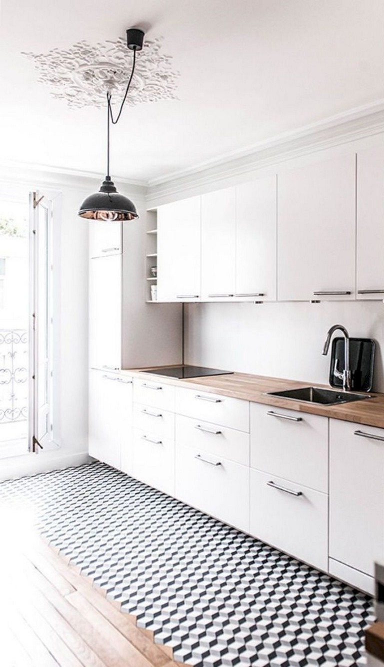 Silver hardware is used as an accent to modern white cabinets with wood countertops