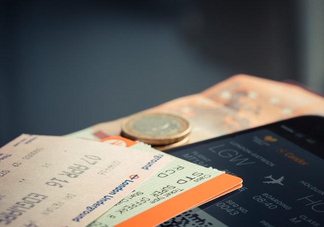 Ticket de passagem sobre uma mesa, ao lado de moedas que simulam troco.