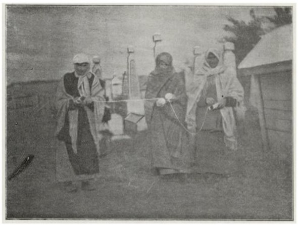 An old black and white image of people holding string and walking around a cemetery