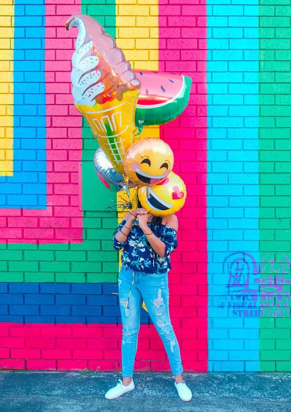 foto de uma mulher em uma parede colorida segurando vários balões de emojis escodendo seu rosto