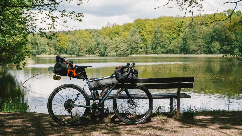 Fahrrad lehnt an einer Bank vor einem See im Grünen