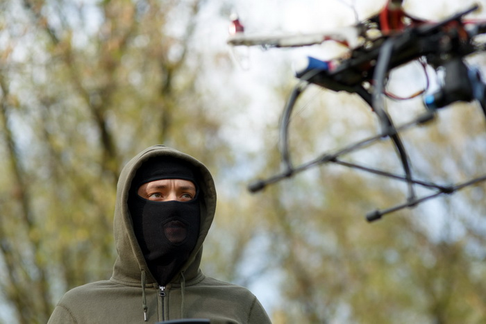 Man in mask operating a drone with remote control. Crime concept