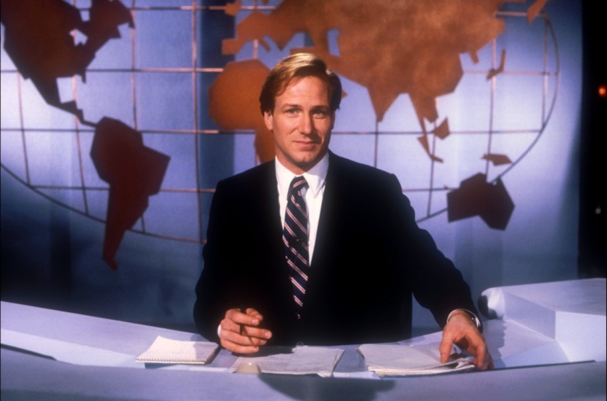 William Hurt as Tom Grunick in Broadcast News. Tom, a red-haired man in a black suit and stripy tie, is sitting at a white news desk with a brown map of the world on the backdrop behind him.