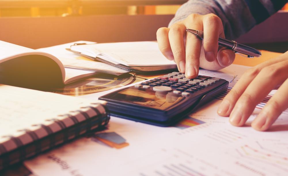 Vista detalhada de uma mão segurando uma caneta e apertando os botões de uma calculadora científica. Podemos identificar, também, diversos papeis. Imagem para ilustrar a reforma de casas.