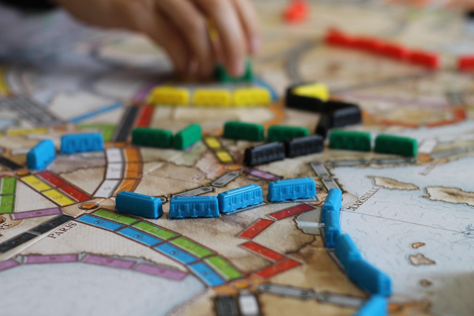 Pessoa jogando um jogo de tabuleiro que tem como peças, vagões de trem
