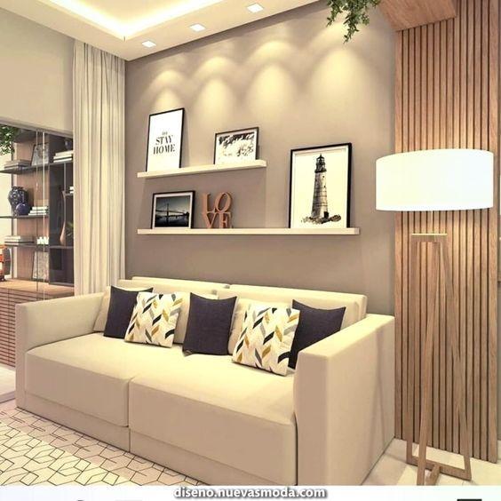 Sala decorada com cores neutras, com sofá creme e almofadas azuis e brancas, prateleiras com quadros decorativos e abajur.