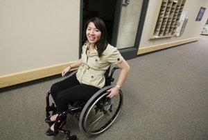Thanh Vo strolls around the offices of Independent Living Resource Center. Vo is a client of the center and she is also interning there as part of her undergraduate work for Wichita State University. She is graduating with a BA in Social Work. She was in a car accident in September 2004 that injured her spinal cord and left her without use of her legs.