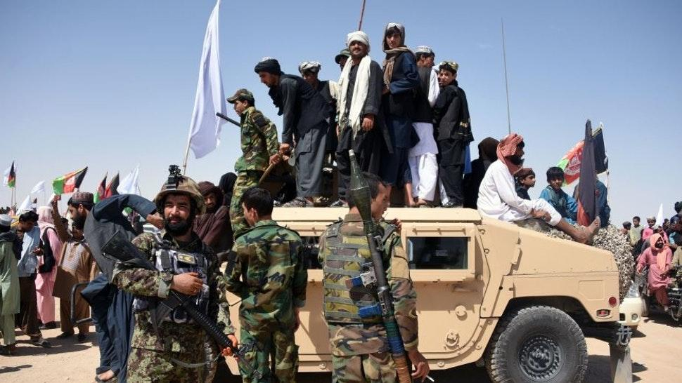In this photo taken on June 17, 2018, Afghan Taliban militants and residents stand on a armoured Humvee vehicle of the Afghan National Army (ANA) as they celebrate a ceasefire on the third day of Eid in Maiwand district of Kandahar province. - Extraordinary scenes of Afghan Taliban and security forces spontaneously celebrating a historic ceasefire showed many fighters on both sides were fed up with the conflict, raising hopes that peace in the war-torn country was possible, analysts said. (Photo by JAVED TANVEER / AFP) / TO GO WITH Afghanistan-unrest-ceasefire,FOCUS by Allison Jackson (Photo credit should read J