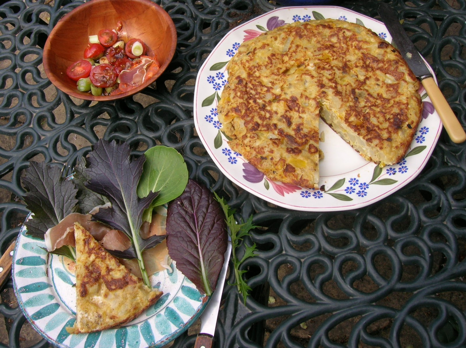 spanish tortilla lunch served on a plate on a garden table. Side salad and chopped tomatoes in a dish beside it.
