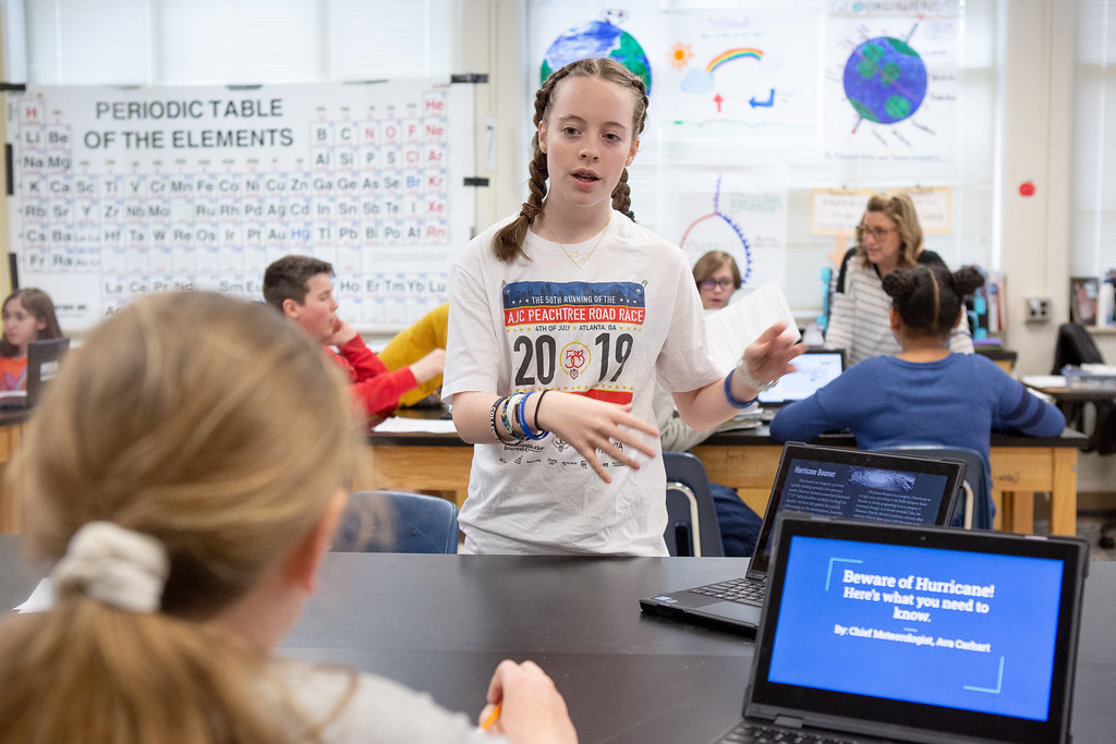 A young girl with braids stands in front of a peer at a computer. They seem to be discussing something in a science classroom. The periodic table of elements hangs on a classroom wall and other students can be seen in in the background.