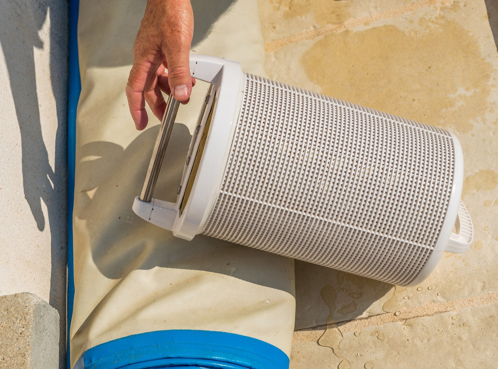 a white cartridge pool filter next to an inground pool