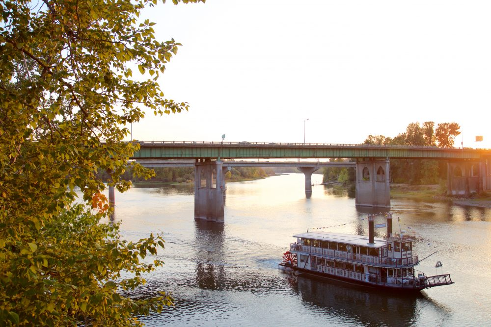 Sunset view of a boat going under the Union Street Railroad Bridge
