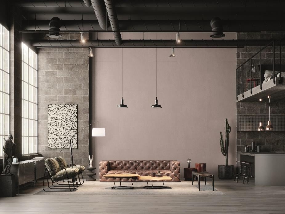 Sala com piso amadeirado cinza, parede de tijolinhos cinza e meio da parede pintado de cinza claro, sofá de couro de marrom, poltronas cinza, mesinha de centro de madeira redonda, luminárias pendentes pretas.