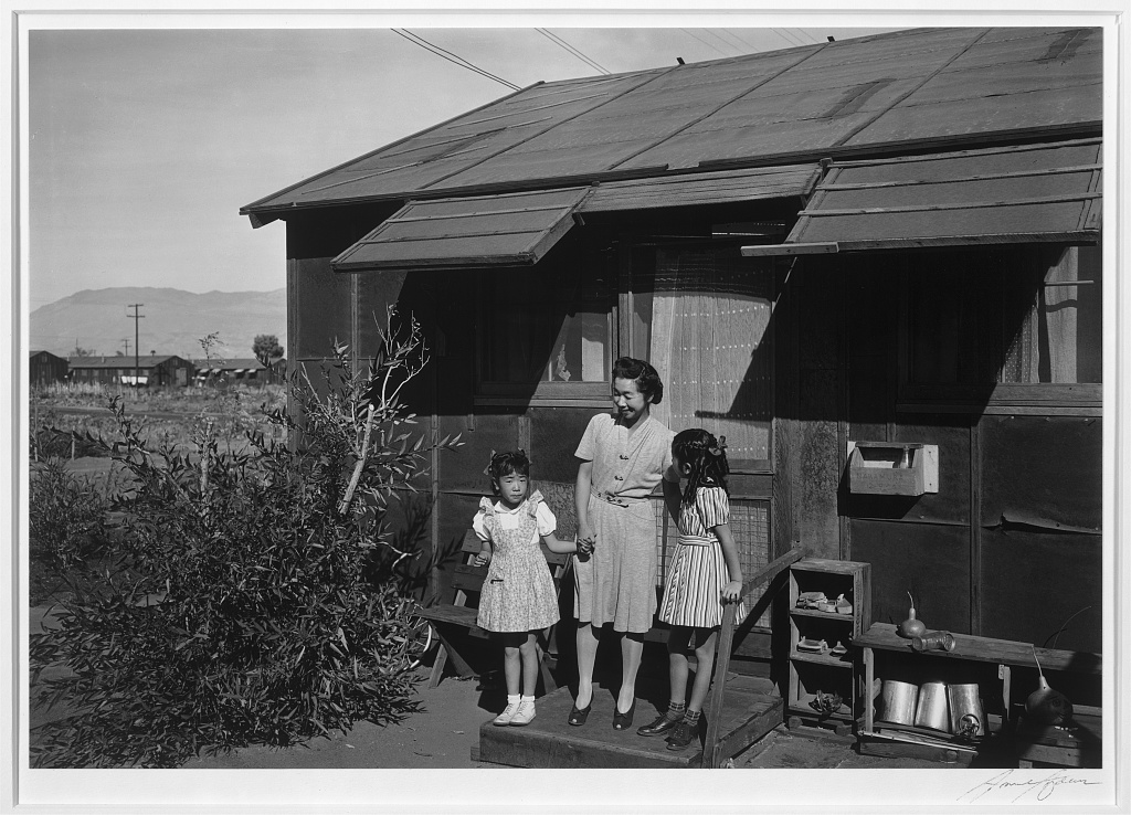 A Japanese American mother and her two daughters standing on the front stoop of their barrack in Manzanar. The mother stands in the middle smiling and looking down at her younger daughter, who faces the camera. The older daughter is leaning on a hand rail and looking up at her mother, with her face turned away from the camera.