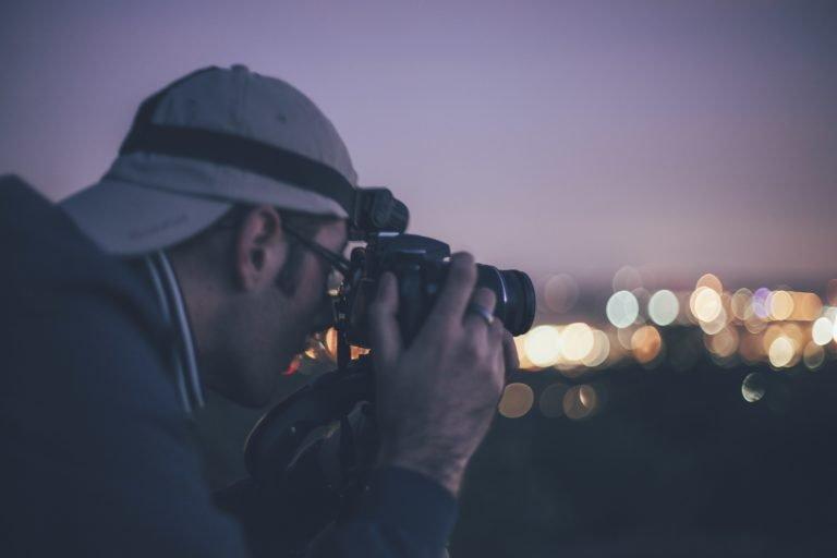 man shooting photos, late night, city