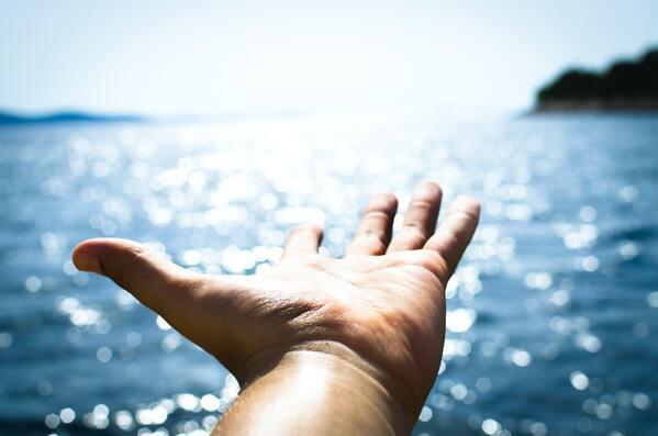 foto de uma mão estendida para o mar
