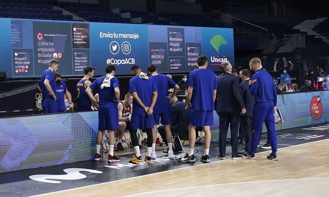 A photo taken during a game's break. In the image appears a basketball team and, in the back, a giant screen displaying two live social media walls.