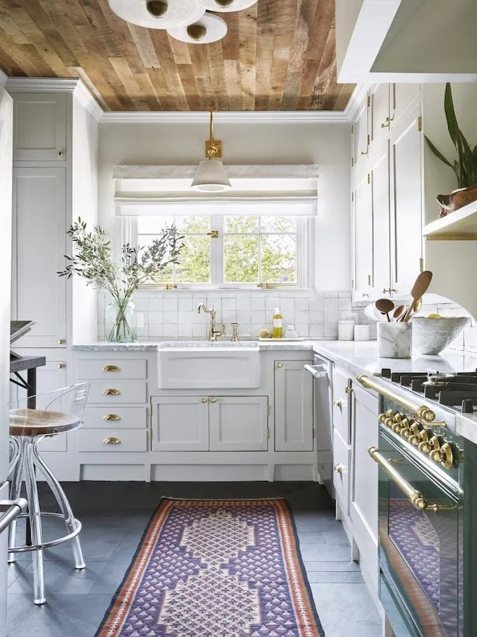 vintage kitchen with white shaker cabinets, tile floors, square white subway tile backsplash, wooden paneled ceiling, oriental rug and vintage stove