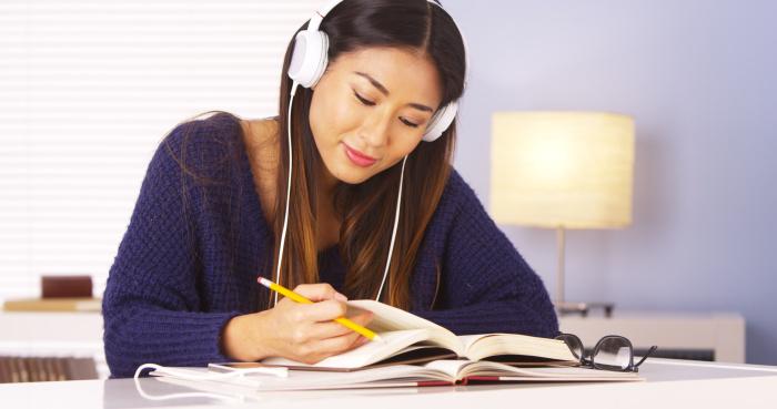 Estudante se preparando para suas aulas de inglês para iniciantes, ouvindo em inglês.
