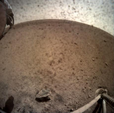 NASA's InSight lander flipped open the lens cover on its Instrument Context Camera (ICC) on Nov. 30, 2018, and captured this view of Mars. Located below InSight's deck, the ICC has a fisheye view, creating a curved horizon. Some clumps of dust are still visible on the camera's lens. One of the spacecraft's footpads can be seen in the lower right corner. The seismometer's tether box is in the upper left corner.