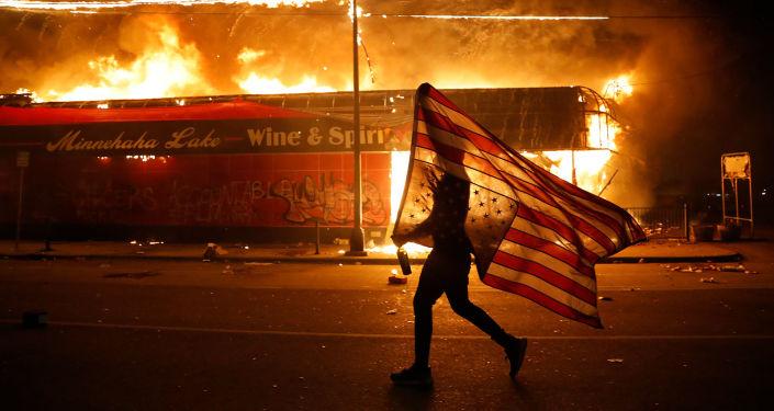 Протестующий с перевернутым флагом США во время демонстрации в связи со смертью Джорджа Флойда, убитого полицейским (28 мая 2020). Миннеаполис