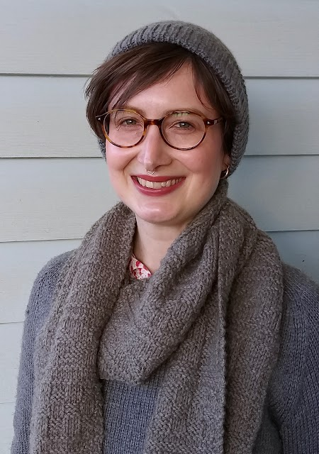 Siobhan stands in front of a weatherboard wall, wearing a grey handknit textured hat, similar style scarf, and plain grey handknit jumper. She is smiling.