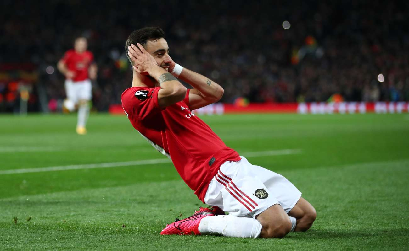 Manchester United's Bruno Fernandes covers his ears and slides on the field in his signature goal-scoring celebration.