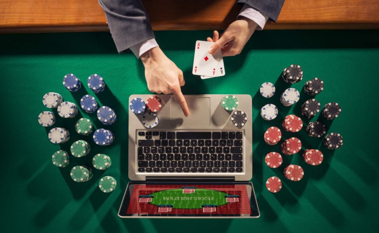 Pria yang bermain poker online dengan laptop, kartu, dan chip di atas meja poker hijau