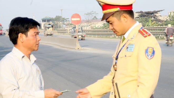 Cảnh sát giao thông kiểm tra GPLX người vi phạm.