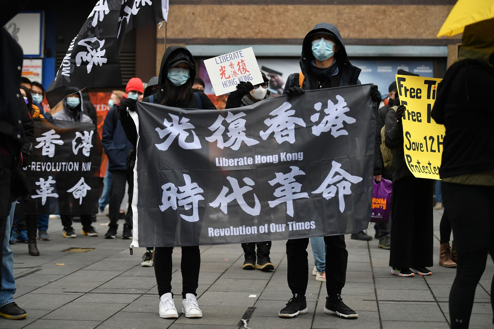Protesters gather with banners at an event organized by Justitia Hong Kong to mourn the loss of Hong Kong's political freedoms, in Leicester Square
