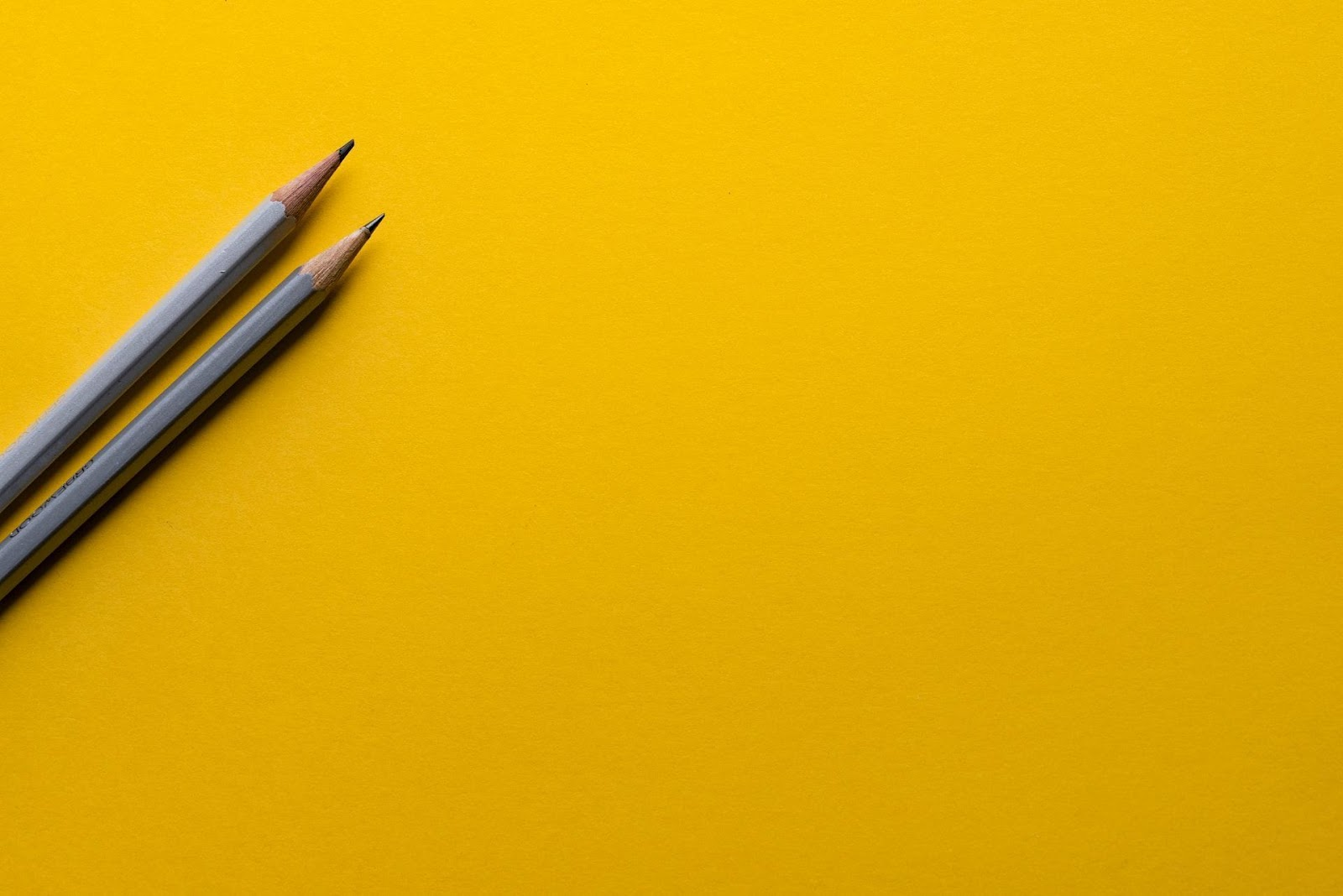 Zwei Bleistifte auf gelbem Papier. Die Erstellung eines Content-Kalenders ist für Blogger ein wesentlicher Bestandteil jeder guten Content-Strategie.