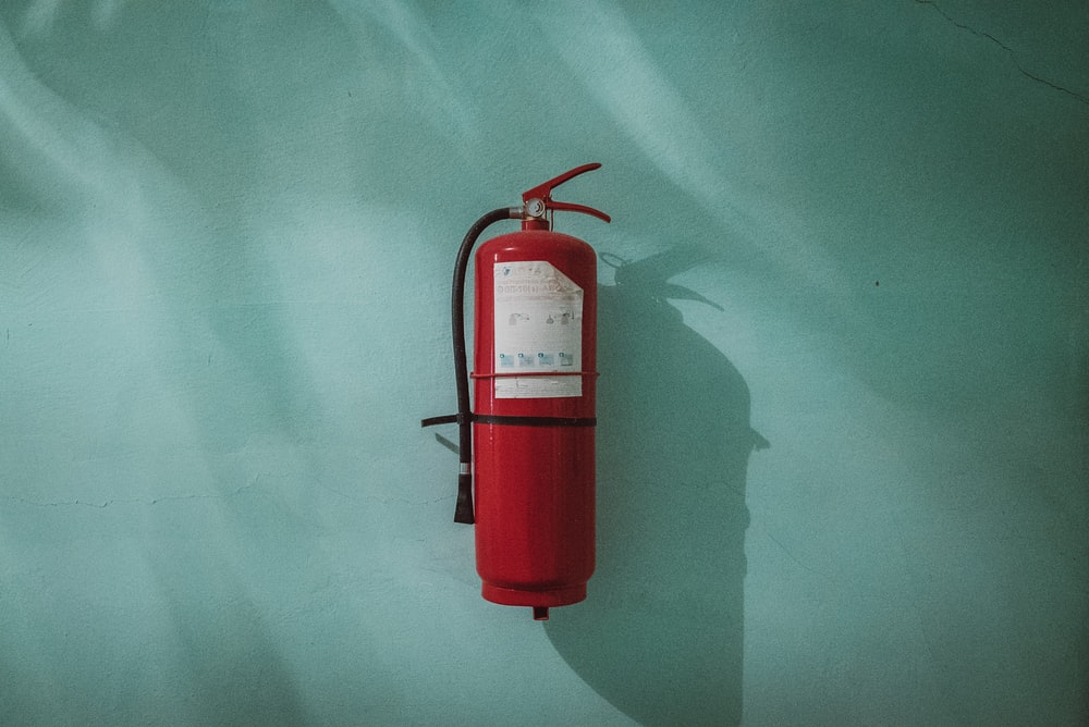 red fire extinguisher on green wall employee safety tips