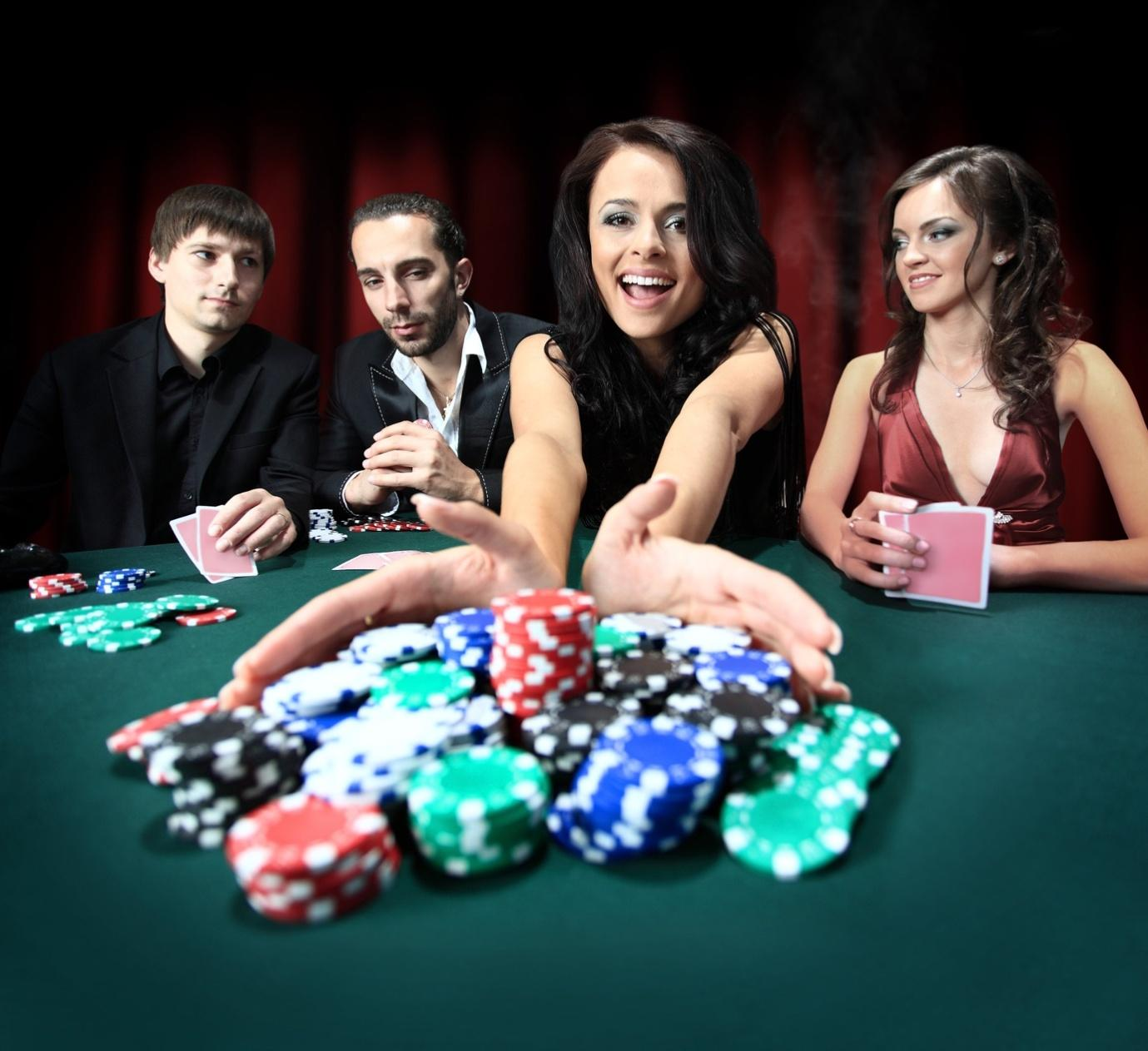A group of people sitting around a table with a board game  Description automatically generated with low confidence