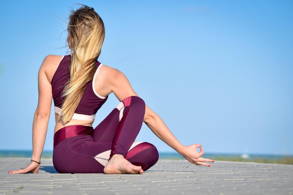 woman in black tank top and purple leggings sitting on wooden floor