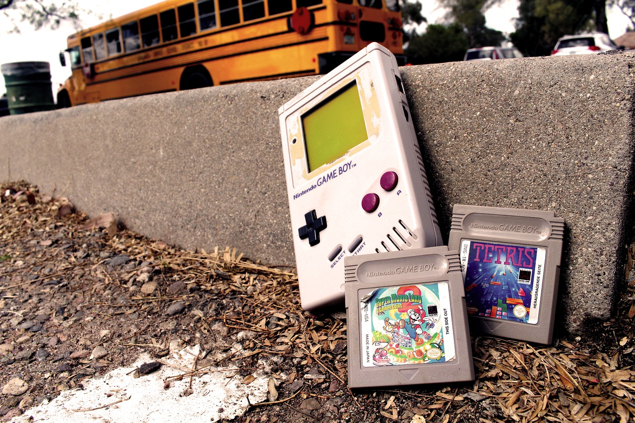 Old gameboy with a yellow schoolbus in background