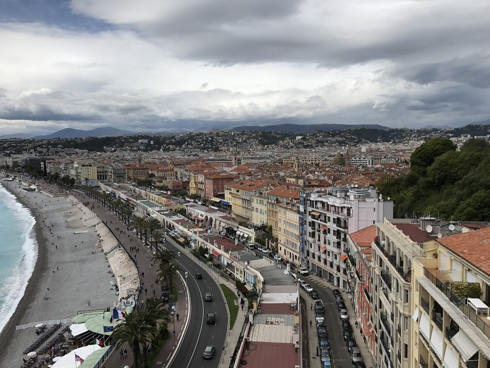 the coast of nice, france. Promenade des anglais, pebble beach, green palm trees and buildings in the distance. cloudy day in cote d'azur. Visit the city during a France road trip