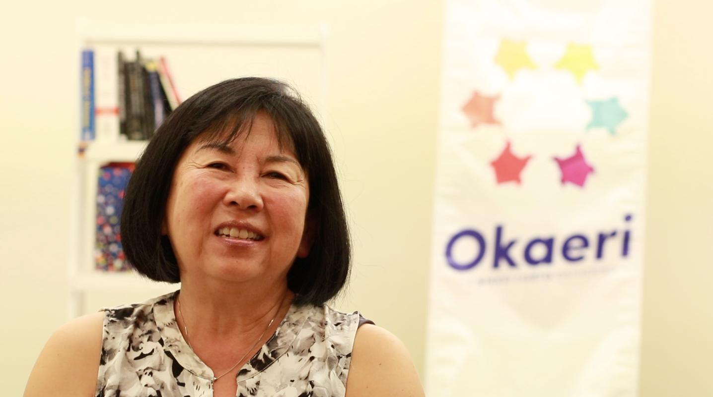 Filipino-Japanese lesbian activist June Lagmay smiling in front of an Okaeri banner.