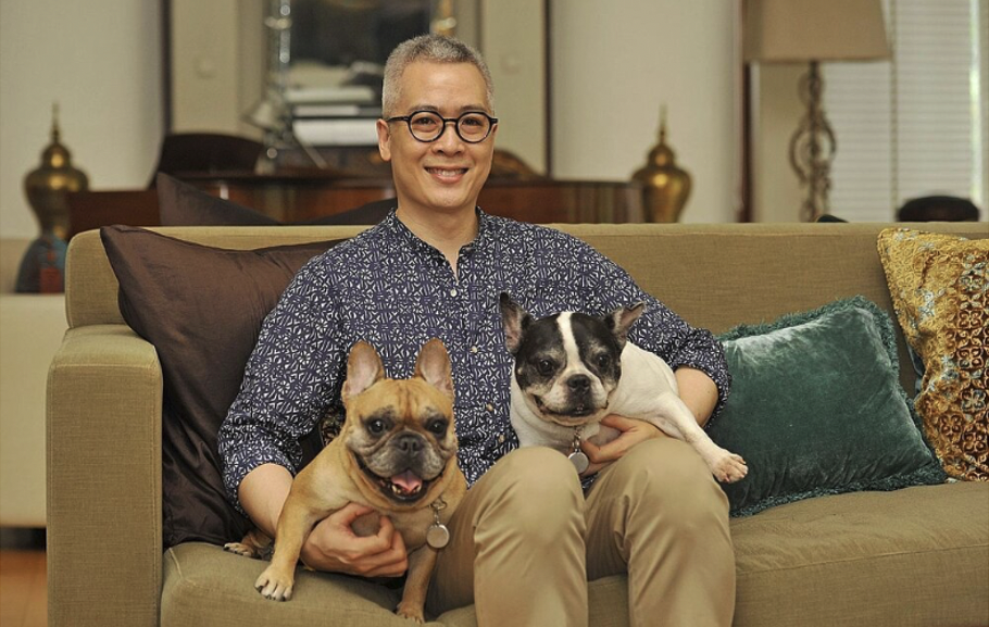 A person sitting on a couch with two dogs  Description automatically generated with medium confidence