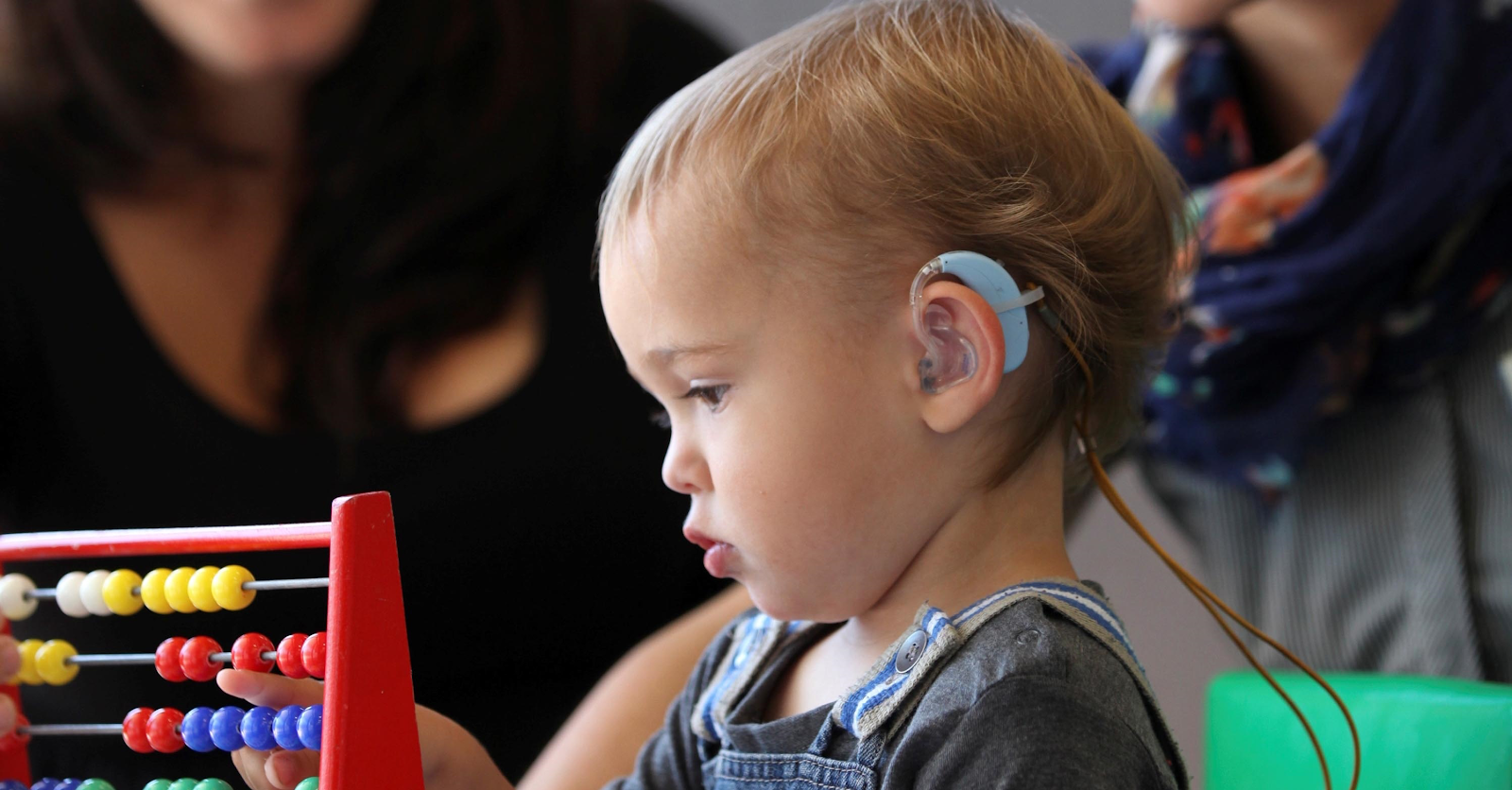 A young child with a hearing aid playing.