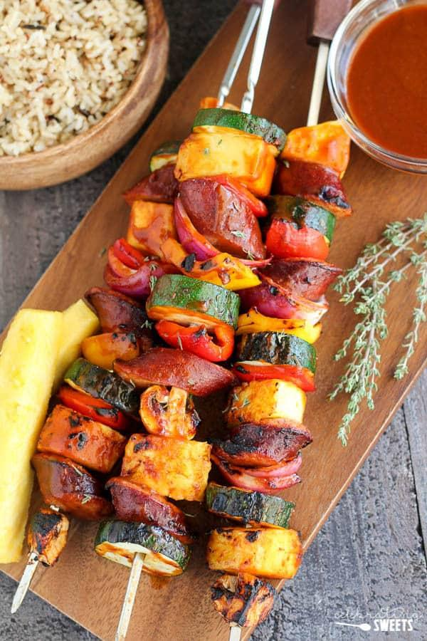 Grilled Sausage and grilled vegetables with pineapple on a wooden cutting board.