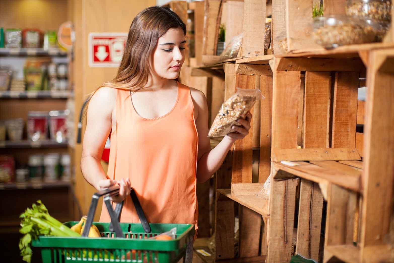 Belle jeune brune regardant une étiquette de produit tout en achetant des provisions au supermarché
